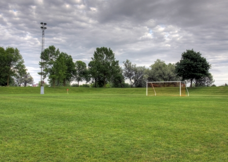 goalline: A cloudy unoccupied soccer field with trees in the background. (HDR photograph)