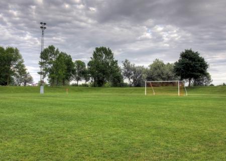 cancha de futbol: Un campo de fútbol nublado desocupada con árboles en el fondo. (Foto HDR) Foto de archivo