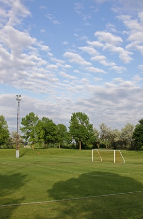 bounds: A mixed sky over an unoccupied soccer field with trees in the background. Stock Photo