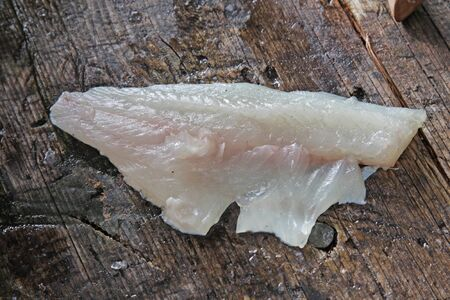 largemouth bass: A fillet from a freshly cleaned Largemouth Bass sitting on an outdoor cleaning board.