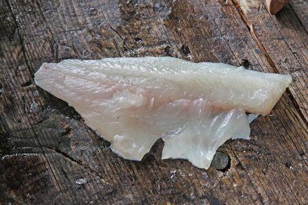 largemouth bass: Un filete de un reci�n limpiado perca americana sentado en un tabl�n de limpieza al aire libre.
