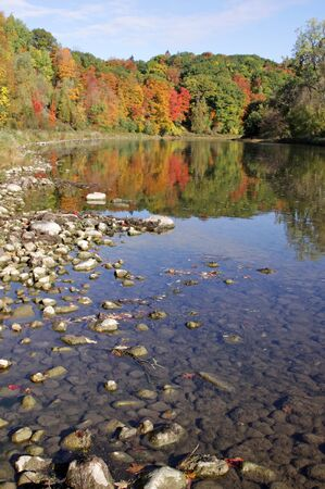 The Grand River with the fall colours reflecting in it.   photo
