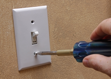 switch on the light: Una mano con un destornillador para atornillar una tapa del interruptor de la luz.