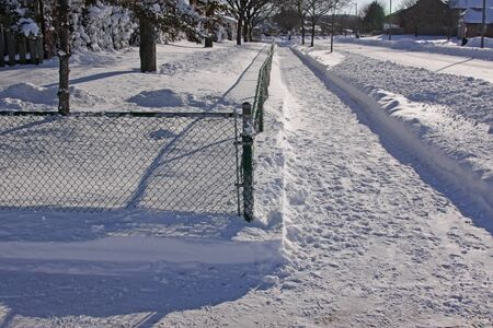 inconvenient: Snow fall in the suburbs, featuring a cleared side walk corner. Stock Photo
