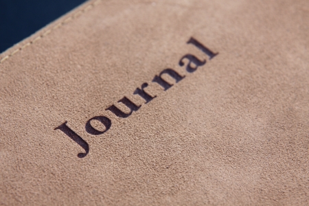 log book: Lettering spelling Journal on the leather case of a journal book.