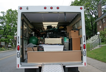 A moving truck full with stuff on the side of the street.