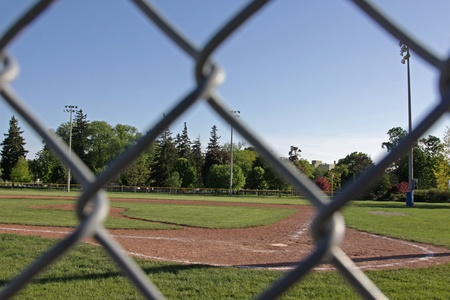 backstop: A shot of an unoccupied baseball field at dusk, shot through the links of the backstop fence.