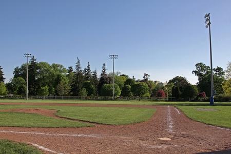 Een schot van een onbezet honkbalveld in de schemering.