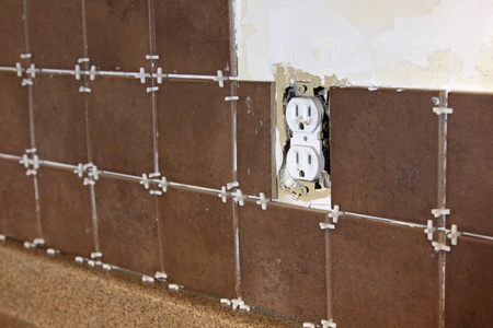 tiling: A kitchen back splash tiling home improvement project half done. Stock Photo