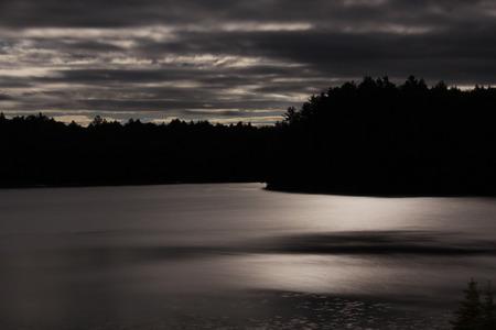 nite: A long exposure of a lake shot at night in Muskoka, Ontario, Canada. Stock Photo