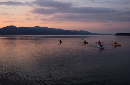 kayaker: A group of kayakers on Lake Champlain during a gorgeous sunset.  Shot from the Vermont side near D.A.R. State Park, looking at the New York side.