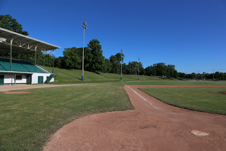 A wide-angle shot of an unoccupied baseball field, with a grandstand on the side.