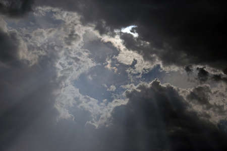 A dramatic shot of the sky with sun peaking through the clouds.
