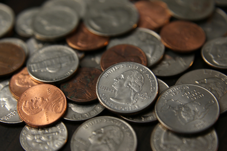 pennies: A pile of US coins sitting on a table, shot with a very shallow depth of field.