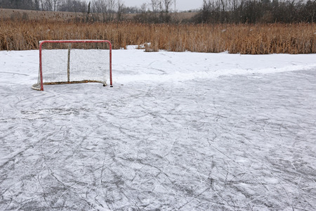 A ice hockey net on an outdoor pond rink.