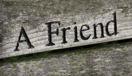 The words A Friend engraved on wood.
