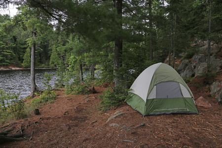 algonquin park: A green tent setup right beside a lake.  Shot in Algonquin Provincial Park, Ontario, Canada. Stock Photo