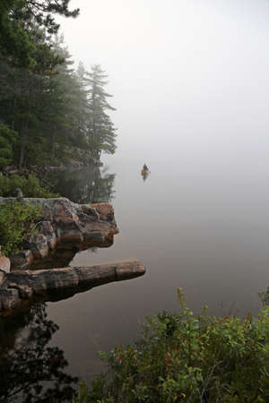 treeline: A canoer paddling on a still lake in Algonquin Provincial Park, in Ontario, Canada. Stock Photo