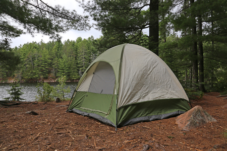 summer nature: A green tent setup right beside a lake.  Shot in Algonquin Provincial Park, Ontario, Canada. Stock Photo
