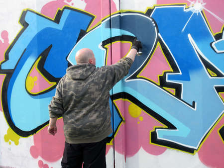vandal: Graffiti artist painting on the wall Editorial