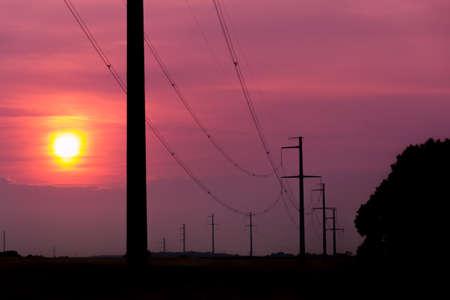 orange sunset: Power lines and pylon during orange sunset