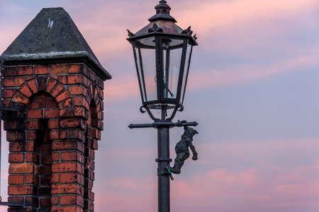 lamp post: Dwarf on a lamp post on bridge in Wroclaw, Poland. Sunrise. Stock Photo