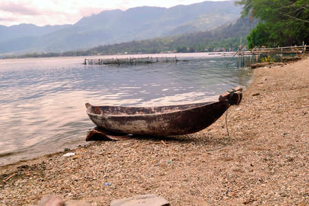 pebles: lonely boat at the edge of lake