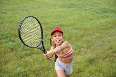 Smiling preteen girl playing tennis Stock Photo
