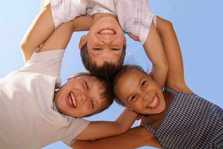 Three preteen friends enjoying summer outdoors on blue sky background photo