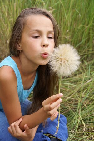 Preteen girl blows at dandelion photo