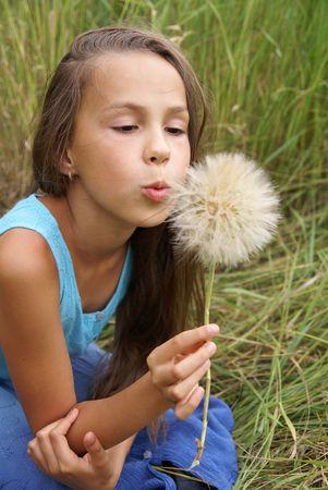 Preteen girl blows at dandelion