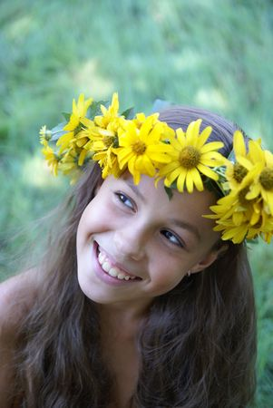 petite: Cheerful preteen girl in yellow flower garland on green grass background