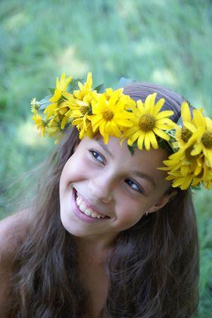 preteen girl: Cheerful preteen girl in yellow flower garland on green grass background