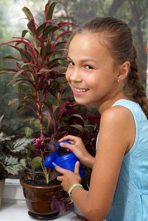 Preteen girl watering plant