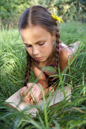cute little girls: Preteen girl reading book on green grass background