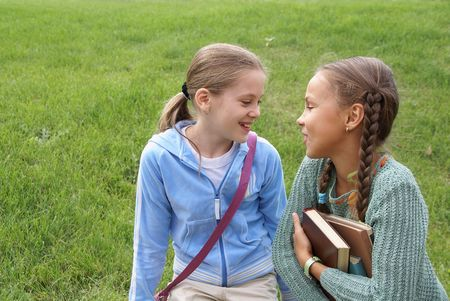 Two preteen school girls talking outdoors