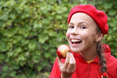 Cheerful preteen girl eats apple on green leaf background photo