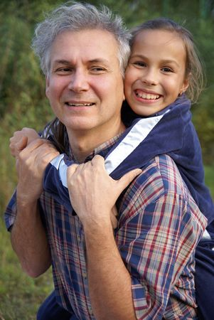 Cheerful father and daughter talking in park photo