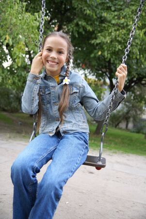 Cheerful preteen girl on a swing on playground Stock Photo