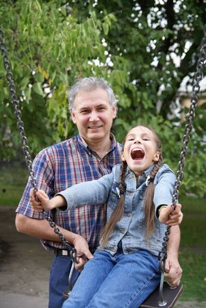 Cheerful father and daughter having fun on playground outdoors photo