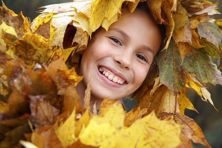 Cheerful preteen girl in yellow leaf garland photo