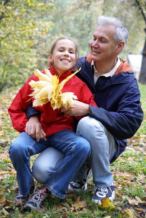 Cheerful father and daughter talking in autumn park photo