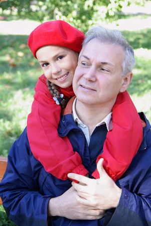 Cheerful father and daughter talking in park