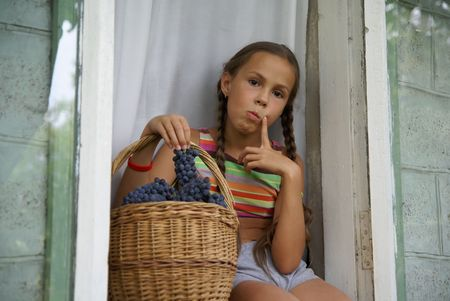 ブドウがいっぱい入ったかごを持つウィンドウで座っている preteen 女の子 写真素材