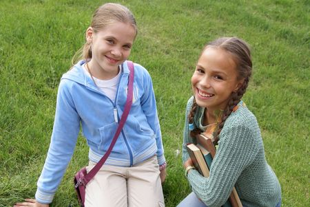 Preteen school girls with books on green grass background outdoors