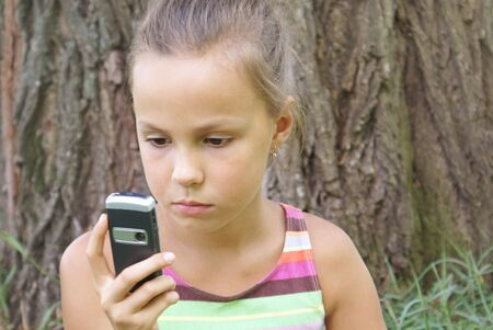 Preteen girl dialing on cell phone Stock Photo - 3897164