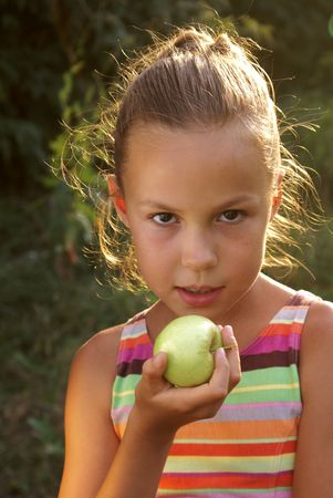 Preteen girl holding a fresh apple