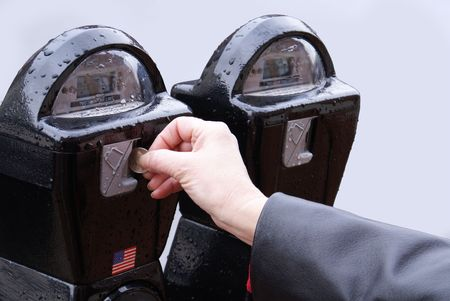 Hand with quarter coin putting money into street digital parking meter to pay for hourly parking  Banco de Imagens