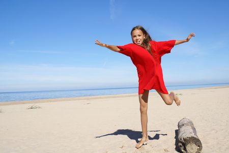 Cheerful preteen girl exercising on a beach                     photo