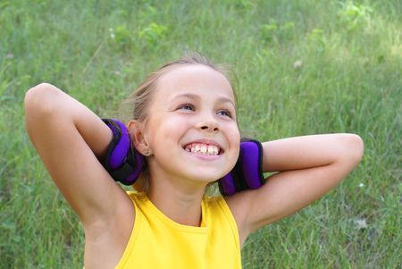 Smiling preteen girl in exersise gear on grass background